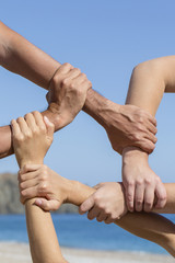 Successful team: hands holding together on blue sky background