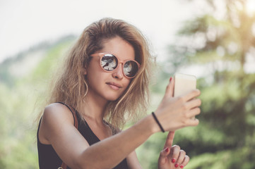 Closeup portrait of young beautiful woman in sunglasses with long blonde curly hair doing selfie photos