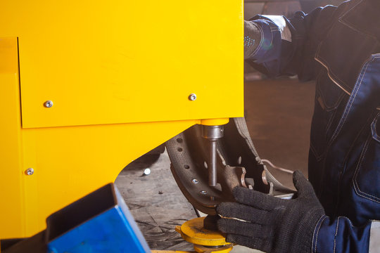 A close-up of a man fitter riveting brake pads for a truck on a modern yellow riveter machine