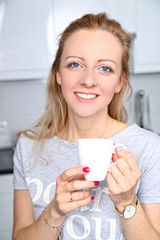 Smiling woman drinking a warm drink