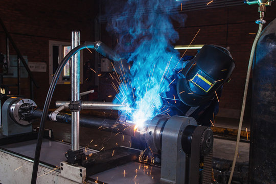 A close-up man is an auto mechanic in a blue uniform in a welding mask cooking metal on an automatic welding machine for repairing cardan shafts in workshop, smoke from  welding machine and sparks fly