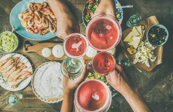 Holiday celebration table setting with food. Flat-lay of friends hands eating and drinking together. Top view of people having party, gathering, celebrating with rose champaign, horizontal composition