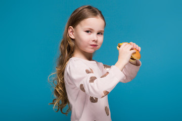 Pretty, little girl in sweater with brunet hair hold a burger