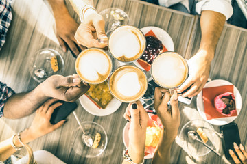 Friends group drinking cappuccino at coffee bar restaurant - People hands toasting at fashion cafeteria with upper view point - Winter drinks concept with men and women at cafe - Warm vintage filter