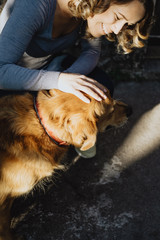 Young beautiful woman stroking a dog and smiling