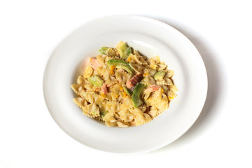 Pasta farfalle with fried meat and vegetables isolated on white. Top view