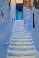 Tuinposter Smal steegje Blue door at the end of a narrow alley with steps, in Chaouen, Morocco