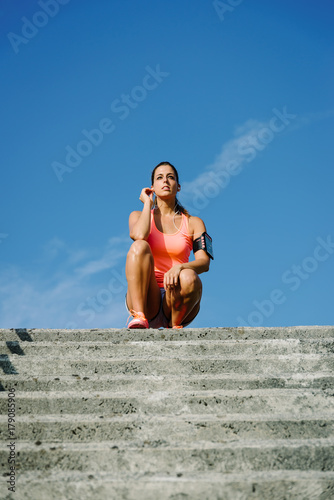 Female runner taking a break after running and climbing