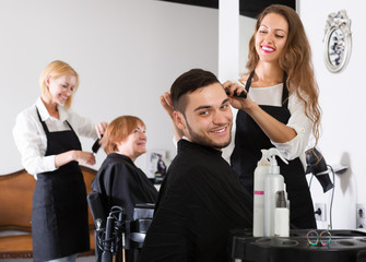 Woman hairdresser doing hairstyle