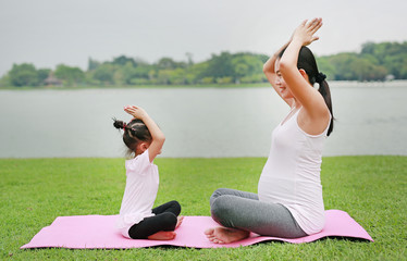 Pregnant mother and her daughter doing yoga in the public park.