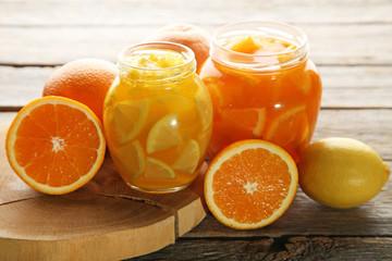 Lemon and orange jam in glass jars on wooden table