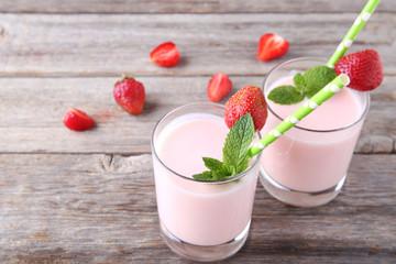 Strawberry yogurt in glass on grey wooden table