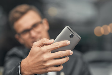 Close-up. A cute guy does selfie on a smartphone. On the street