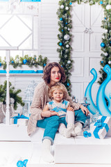 beautiful mother and charming daughter, sitting next to a Christmas tree and Christmas balls in warm stylish sweater and jeans