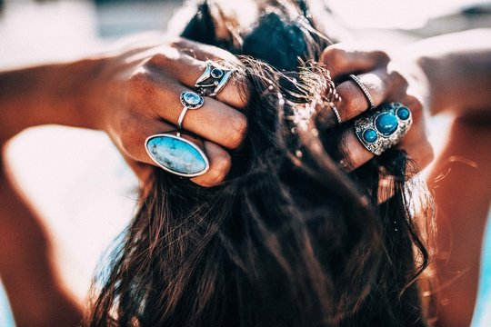 Close up of Women with bohemian style jewellery rings on hands