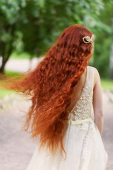 Beautiful red-haired girl with long curly hair in the bride, in a long lace dress. A natural beauty.