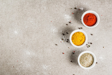 Various spices and seasonings. Cooking background.  Turmeric, curry, paprika, pepper, chili, dried basil, salt, fresh chili, thyme. Grey stone background. Copy space top view