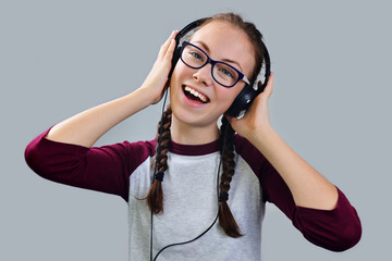 Beautiful young girl listening to music on headphones.