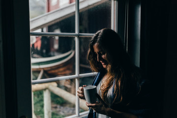 Woman with mug near window