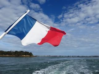 Drapeau français flottant à l'arrière d'un bateau en mer (France)