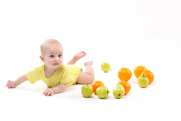 cute smiling healthy child lies on a white background among fruit
