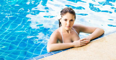 Young and sporty woman in swimsuit. Girl relaxing in a pool at summer.