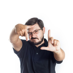 Portrait of 30 years old man with glasses and beard. Photographer or operator checking composition in frame of his finger