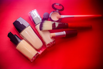 Brush for make-up with cream base shadows. Smears of foundation for three different skin tones on a red background