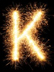 Sparkler firework light alphabet K isolated on black