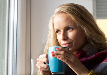 Woman drinking tea beside window in winter