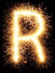 Sparkler firework light alphabet R isolated on black