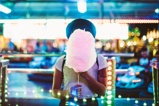 Stylish woman covering face with sugar cloud