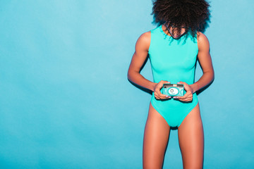 girl in blue bodysuit with camera