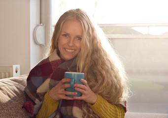 Girl drinking tea on sofa in winter time