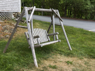 A wooden swing sits on a hill for relaxing
