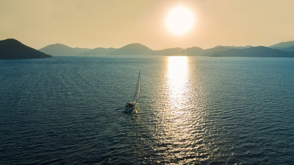 Boat sailing into the sun in Mediterranean Sea