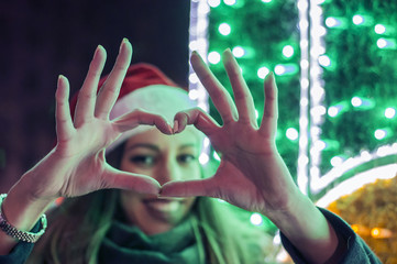 Close up of happy young woman showing heart with hands