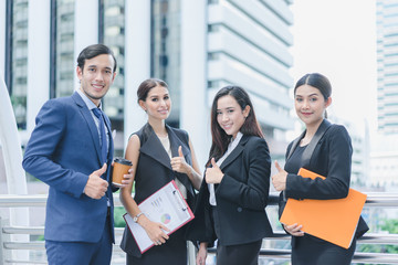 Professional business team holding document and looking forward confidently standing outdoors in cityscape background