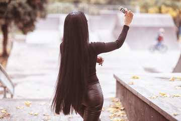 beautiful young brunette girl with long hair, wearing in leather pants stand back and making selfie on smartphone