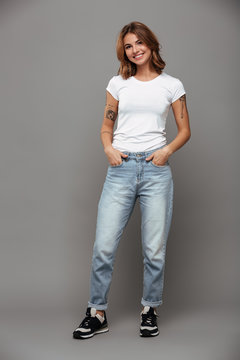 Full length photo of cute brunette woman with hands in her pockets wearing trendy mom jeans and white tshirt, looking at camera