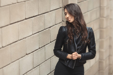Portrait of beautiful smiling brunette, fashion and stylish standing near the wall. A curly hairstyle woman in total black look with leather jacket and dress.