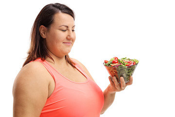 Overweight woman looking at a bowl of salad