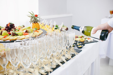 A beautiful fruit bar serving a festive table. The waiter pours champagne in wine glasses