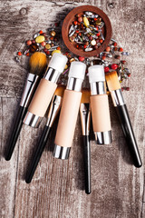Cosmetics products and brushes in conceptual image over wooden background. Beauty accessories. Professional products