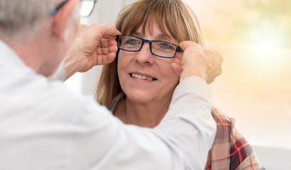 Mature woman testing new eyeglasses, light effect