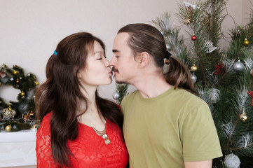 pregnant wife and husband kissing each other, happy young family portrait in Christmas interior, man and woman togetherness