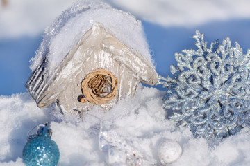 A birdhouse, a house for birds in the snow a Christmas tree toy and a silvery shiny snowflake decor. Merry Christmas and Happy New Year!