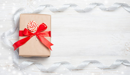 Gift box with red bow on wooden table. Christmas background with festive decoration. Place for your text. copyspace. top view, flat lay