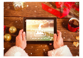Santa Holding Tablet at Wooden Desk Mockup 1