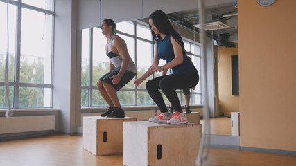 Sportive young woman and muscular man fitness instructor doing box jump exercise during a workout at the gym